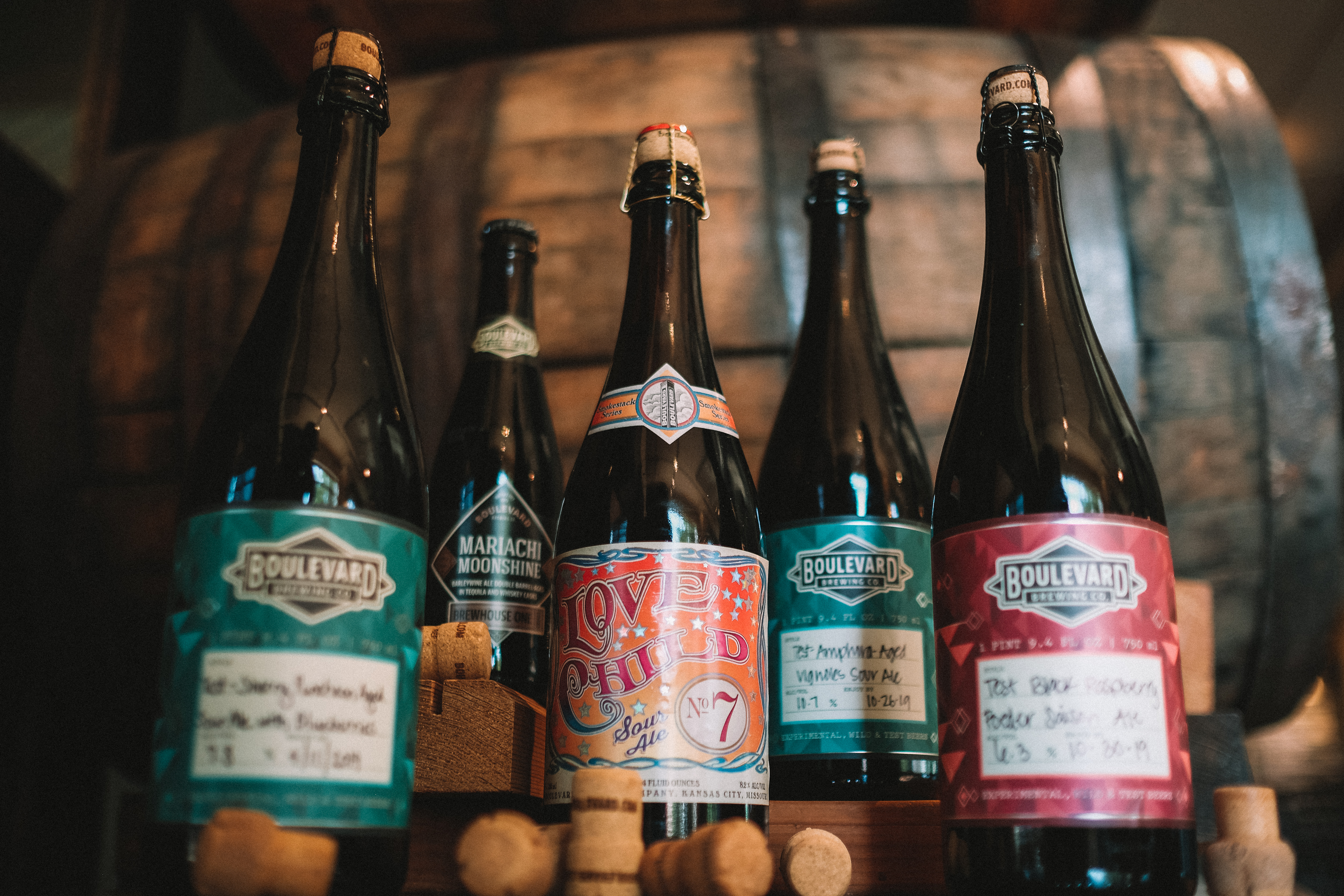 Collection of Boulevard Sour Beers in front of whiskey barrels