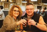 Two people saying cheers with beers in the Tours & Rec Tasting Room