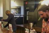 Bartenders pour beer in the Tours & Rec Tasting Room